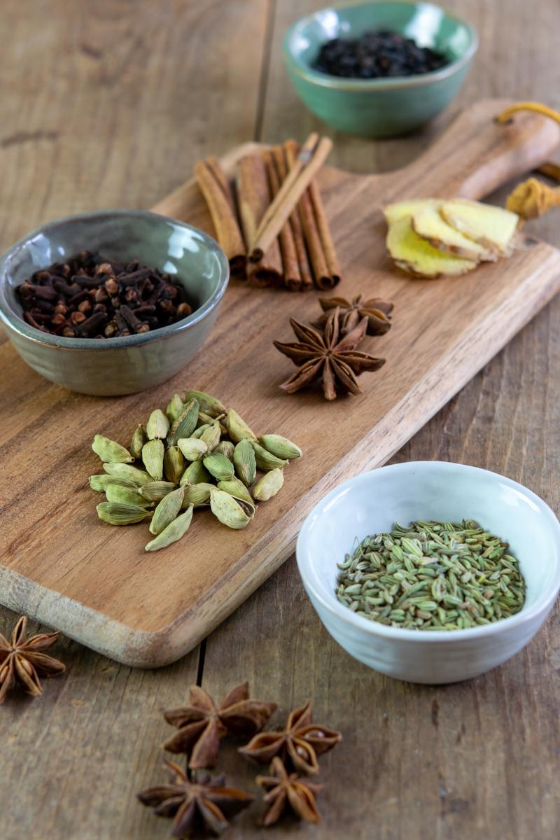épices entières comme l'anis étoilé, la cardamome verte, les graines de fenouil, les grains de poivre noir, les bâtons de cannelle et les clous de girofle